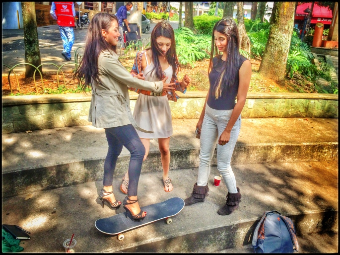 Three cute Colombian girls trying out my skateboard.